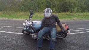 Мотоциклист поднимает мотоцикл
