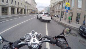 Белая машина перед мотоциклом